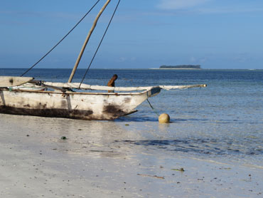 boat on the beach with Mnemba in the background