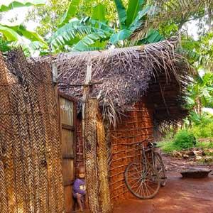 Barn och cykel vid en kokospalmshydda
