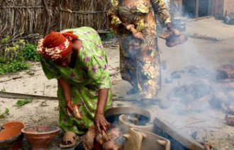 Jambiani Pottery women making a fire to burn their pottery